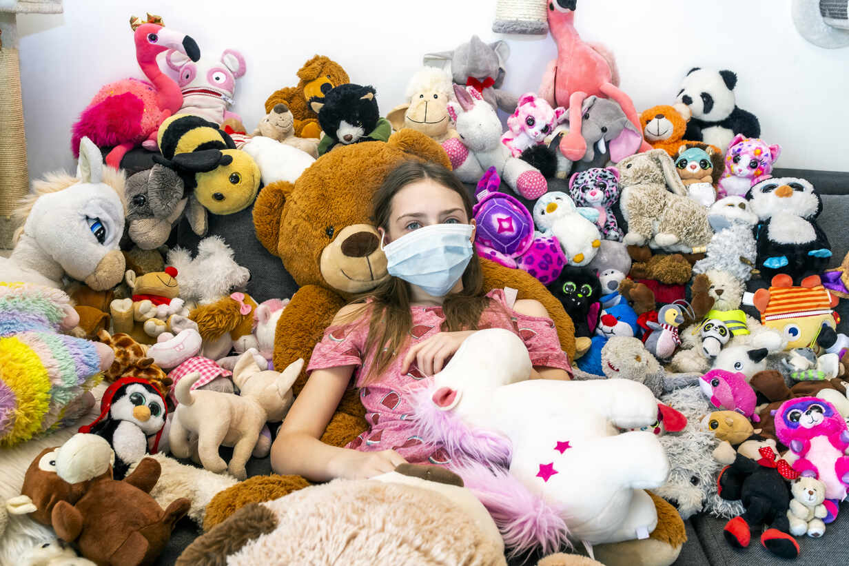 Girl with face mask, sitting on couch, covered in cuddly toys - SARF04516 - Sandra Roesch/Westend61