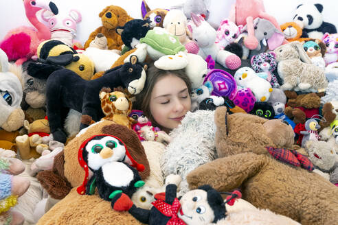 Girl sitting on couch, covered in cuddly toys - SARF04519