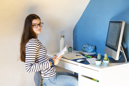 Portrait of schoolgirl sitting at desk at home doing homework - LVF08745