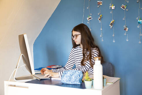 Girl sitting at desk at home doing homework on computer - LVF08748