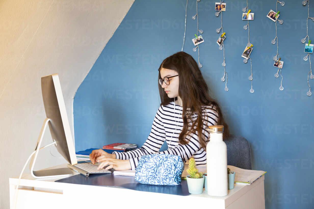 Girl sitting at desk at home doing homework on computer - LVF08748 - Larissa Veronesi/Westend61