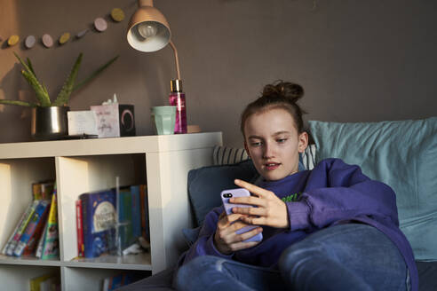 Portrait of girl lying on bed at home looking at smartphone - AUF00329