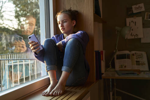 Girl sitting barefoot on window sill in the evening looking at smartphone - AUF00332