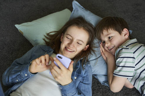 Portrait of laughing girl and her little brother lying together on the floor  looking at smartphone - AUF00338