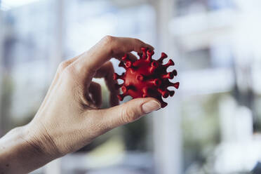 Hand holding model of corona virus, close up - MFF05373