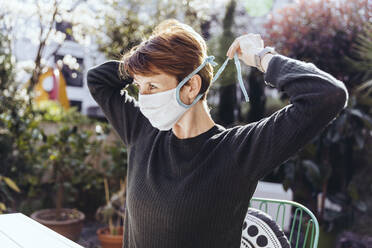 Woman siting in garden, putting on face mask - MFF05382