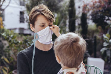 Littley boy helping his mother to put on a face mask - MFF05391