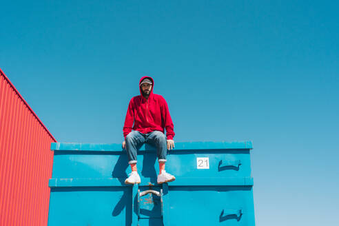 Young man wearing red hoodie, sitting on edge of blue container - ERRF03120