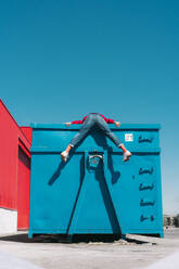 Young man hanging over edge of blue container, rear view - ERRF03123