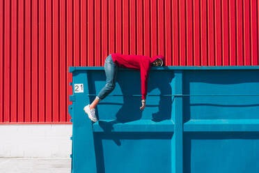 Young man wearing red hooded jacket lying on edge of container - ERRF03129