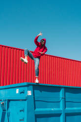 Young man wearing red hooded jacket balancing on edge of container in front of red wall - ERRF03132
