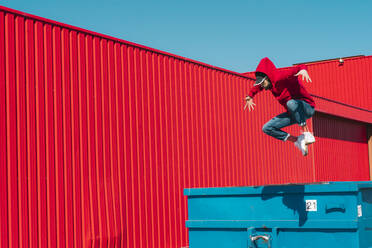 Young man wearing red hooded jacket jumping from edge of container in front of red wall - ERRF03135
