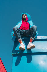Young man wearing red hooded jacket sitting on container against blue sky - ERRF03144