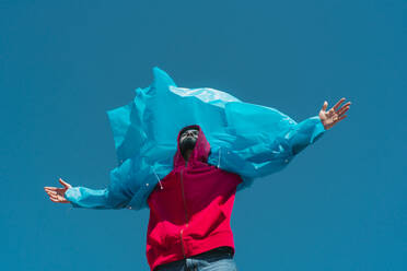Young man wearing plastic rain coat, stanind in gthe wind with arms outstretched - ERRF03147