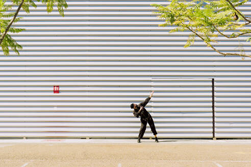 Man wearing black overall posing in front of industrial building - ERRF03150