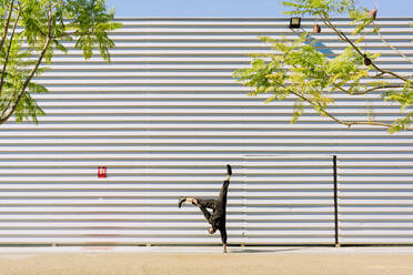 Man wearing black overall doing handstand in front of industrial building - ERRF03153