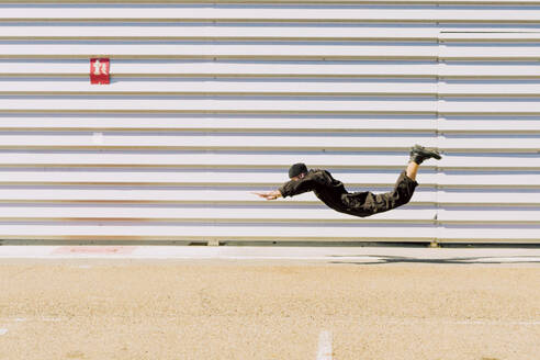 Man wearing black overall in the air in front of industrial building - ERRF03156