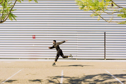 Man wearing black overall jumping in the air in front of industrial building - ERRF03159