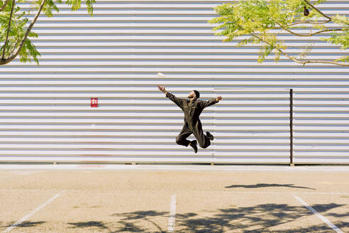 Man wearing black overall jumping in the air in front of industrial building - ERRF03162
