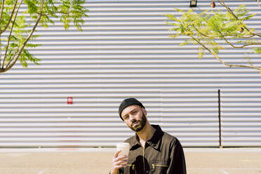 Portrait of pensive man with coffee to go in front of industrial building - ERRF03168