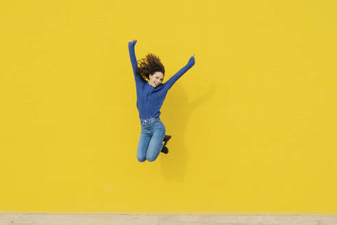 Young woman jumping in the air in front of yellow background - JCZF00030