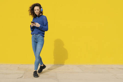Portrait of young woman with headphones in front of yellow background looking at cell phone - JCZF00033