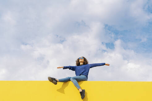 Happy young woman sitting on yellow wall against cloudy sky looking up - JCZF00036