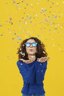 Portrait of young woman with mirrored sunglasses blowing confetti in the air in front of yellow background - JCZF00042