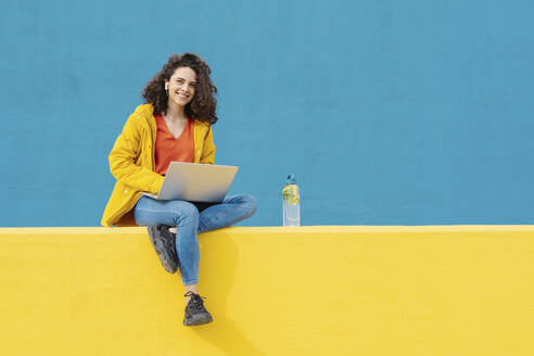 Portrait of smiling young woman with earphones and laptop sitting on yellow wall - JCZF00048