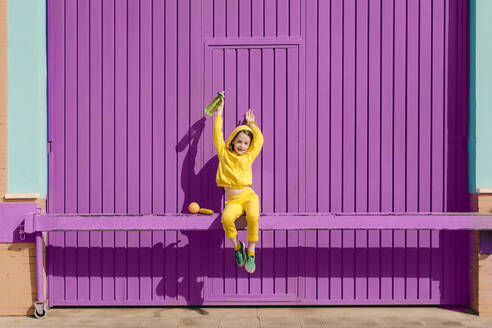 Happy little girl dressed in yellow sitting on bar in front of purple garage door - ERRF03173