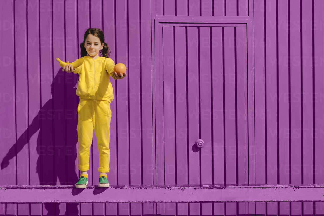 Portrait of little girl dressed in yellow standing in front of purple background offering fruits - ERRF03176 - Eloisa Ramos/Westend61