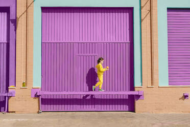 Little girl dressed in yellow balancing with orange on bar in front of purple garage door - ERRF03179