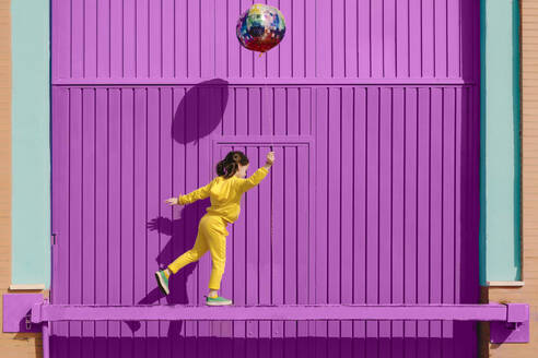 Little girl dressed in yellow balancing on bar in front of purple garage door holding balloon - ERRF03182