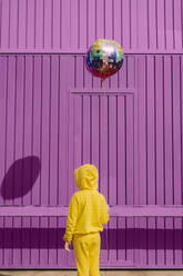 Back view of children dressed in yellow holding balloon in front of purple background - ERRF03185