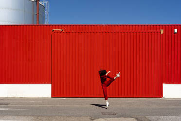 Woman dressed in red overall jumping in the air in front of red roller shutter - ERRF03188