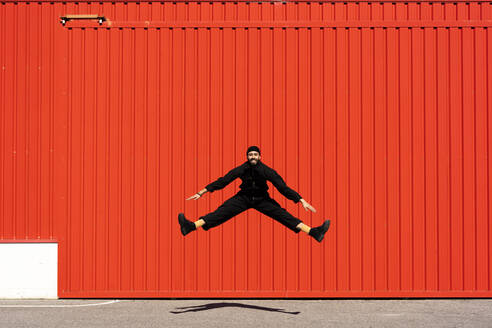 Smiling man dressed in black jumping in the air in front of red roller shutter - ERRF03191