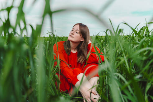 Portrait of woman wearing red dress sitting in a field with eyes closed - ERRF03229