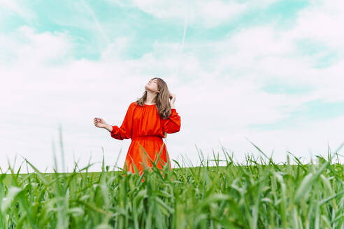 Woman wearing red dress standing in a field with eyes closed - ERRF03232