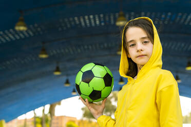 Portrait of little girl wearing yellow hooded jacket holding soccer ball - ERRF03247