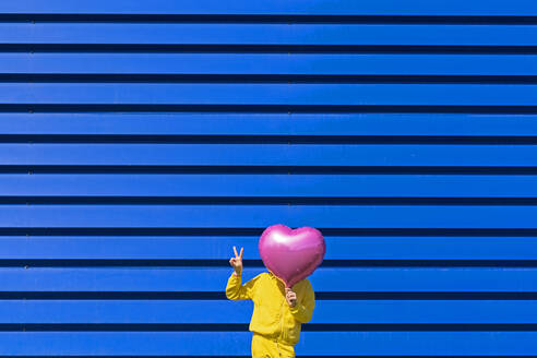 Little girl standing in front of blue background hiding behind pink balloon and showing victory sign - ERRF03250