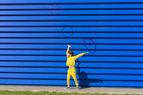 Little girl wearing yellow tracksuit throwings gymnastic rings in the air in front of blue background - ERRF03253