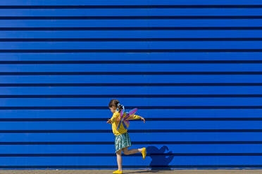 Little girl with colourful butterfly wings balancing on one leg in front of blue background - ERRF03259
