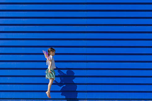Little girl with colourful butterfly wings jumping in the air in front of blue background - ERRF03262
