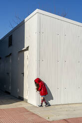 Little girl wearing red rain coat hiding behind a corner - ERRF03268
