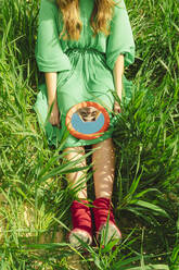 Crop view of young woman wearing green dress sitting on a field looking at mirror - ERRF03277