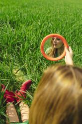Mirror image of young woman sitting on a field - ERRF03280