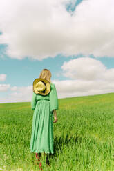 Back view of woman wearing green dress standing on a field - ERRF03283