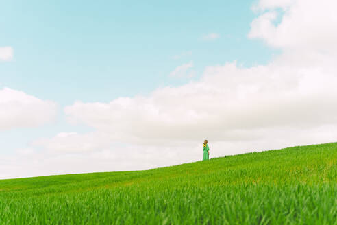Back view of woman wearing green dress standing on a field looking at distance - ERRF03286
