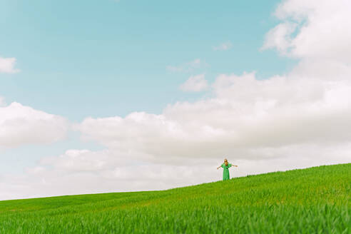 Back view of woman wearing green dress standing on a field - ERRF03289