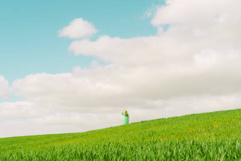 Back view of woman wearing green dress and summer hat standing on a field looking at distance - ERRF03292